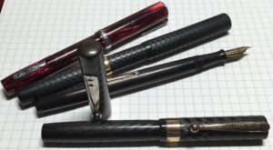 Black chased hard rubber (BCHR) pens and a red Parker